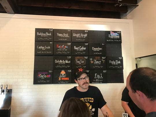 At Abridged Beer Company, orders are placed at the bar, where a colorful chalkboard displays the brewery's rotating selection of beers.