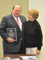 Board president Jim Roy presents Rae Logan with a plaque