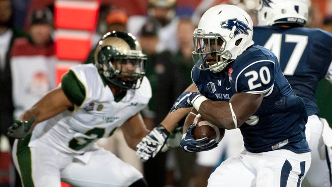 Dec. 29, 2015; Tucson; Nevada Wolf Pack running back James Butler (20) runs the ball under pressure from Colorado State Rams linebacker Cory James (31) during the second quarter of the Arizona Bowl at Arizona Stadium.Sports