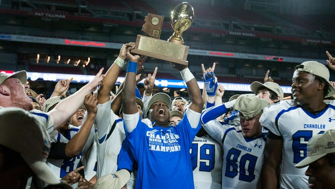 The Chandler Wolves hold up the division one State Championship trophy after winning against the Hamilton Huskies, 28-7, Nov. 28, 2014 in Glendale, Ariz. at the University of Phoenix Stadium.
