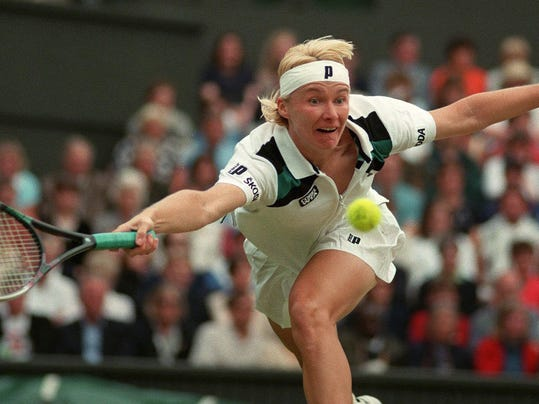 FILE - In this July 4, 1998 file photo, Jana Novotna of the Czech Republic, stretches to make a return to Nathalie Tauziat of France, during the women's singles final match on Wimbledon's Centre Court.  Women's Tennis Association says 1998 Wimbledon champion Jana Novotna has died at age 49. (AP Photo/Rui Vieira, File)