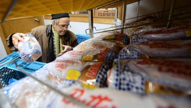 Manna For Life volunteer Joe Garsow restocks the bread at Manna For Life on University Avenue in Green Bay on Dec. 16.