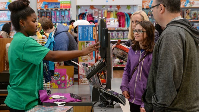 Hallie Brown, left, checks out items for Dana Kossin, middle, and her father Brian Kossin of Greenville during Black Friday at the Toys R Us on Woodruff Road in Greenville.
