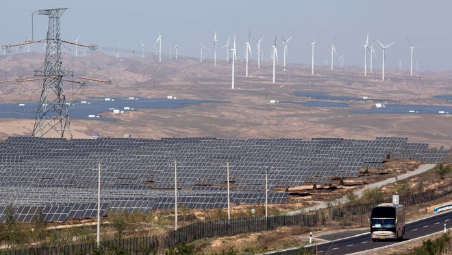 A bus moves past by solar power and wind power farms in northwestern China's Ningxia Hui autonomous region.
