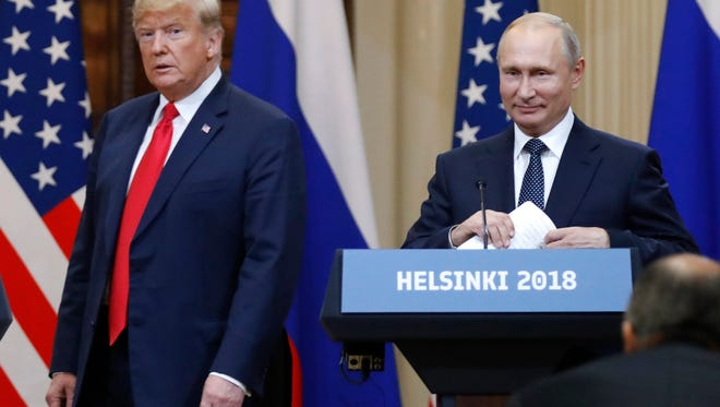 President Donald Trump, left, and Russian President Vladimir Putin arrive for a press conference after their meeting at the Presidential Palace in Helsinki July 16, 2018.