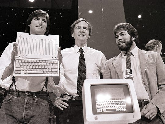 In this April 24, 1984, file photo, from left, Steve Jobs, chairman of Apple Computers, John Sculley, president and CEO, and Steve Wozniak, co-founder of Apple, unveil the new Apple IIc computer in San Francisco.