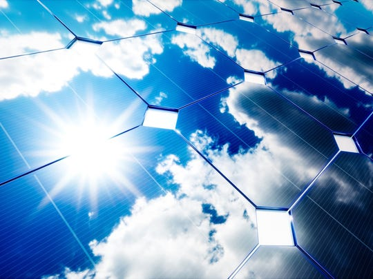 Close-up photo of a solar panel reflecting the sun and patchy clouds against a deep blue sky.