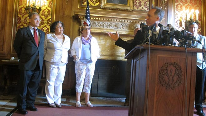 Republican Assembly Speaker Robin Vos, right, motions to Democratic Reps., from left, Peter Barca, JoCasta Zamarripa and Christine Sinicki, on July 28 at a news conference to announce a bill to pay for a new $500 million Milwaukee Bucks arena.