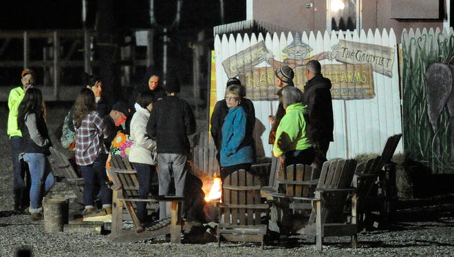 People gather around a fire at Harvest Hill Farms after a hayride accident that injured multiple people Saturday.
