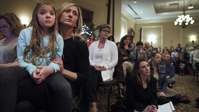 Becky Cincebox of Pittsford listens with her daughter Brooke Cincebox, 8, on her lap during a parent information meeting about NYS standardized testing and Common Core at Mario's Via Abruzzi on Monday evening, April 6, 2015.