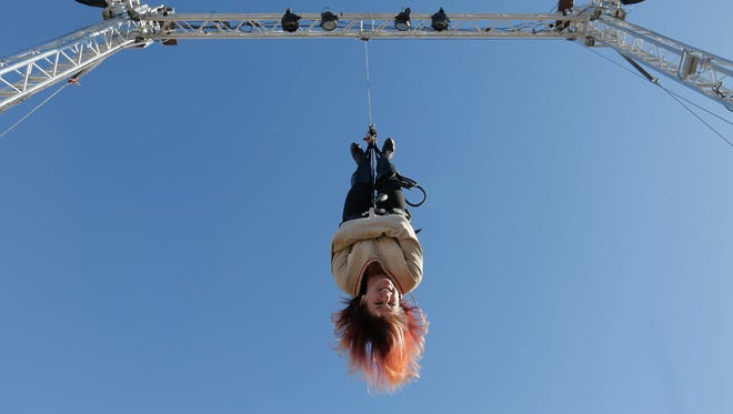 Kristen Johnson, aka Lady Houdini, is hoisted into the air before escaping her straitjacket Sunday at the Sun City Fair.