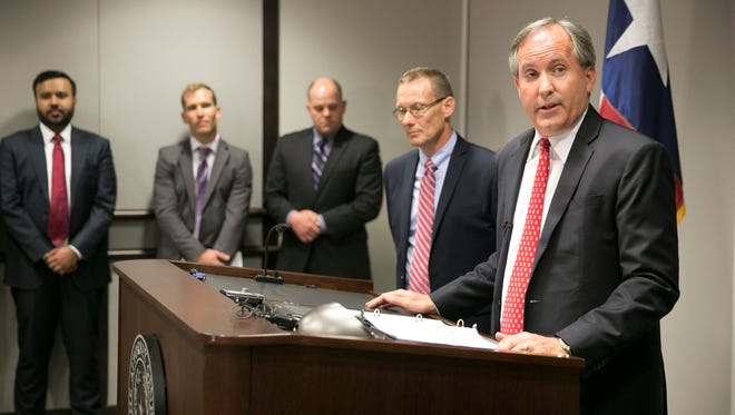 FILE - In this May 25, 2016file photo, Republican Texas Attorney General Ken Paxton,right, announces Texas' lawsuit to challenge President Obama's transgender bathroom order during a news conference in Austin, Texas. Texas and 11 other states will ask a federal judge Friday, Aug. 12, 2016, to halt an Obama administration directive on bathroom rights for transgender students in U.S. public schools. The Obama administration told U.S. public schools in May that transgender students must be allowed to use bathrooms and locker rooms consistent with their chosen gender identity.  (Jay Janner/Austin American-Statesman via AP)