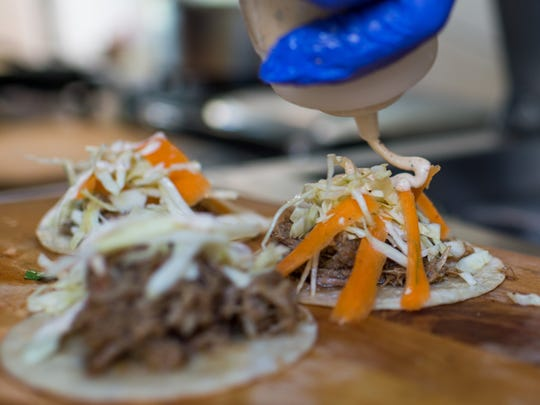 Jerk pork tacos are topped with a cabbage carrot slaw and jerk mayo by Nick Glenn, co-owner of the Live Action Deli food truck, during lunch near the UL campus on West St. Mary Street in , La., Wednesday, Nov. 11, 2015.