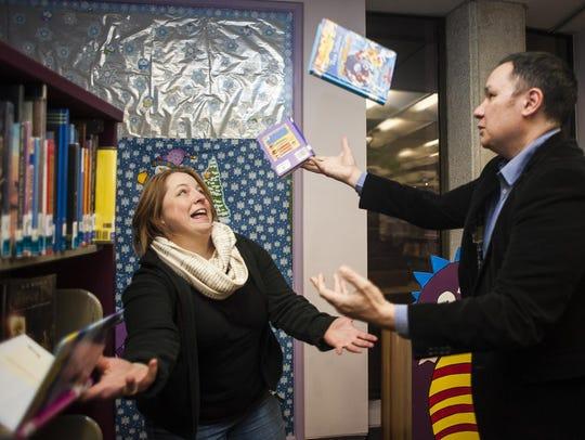 Jamie Ford juggles books while Leesha, his wife, tries
