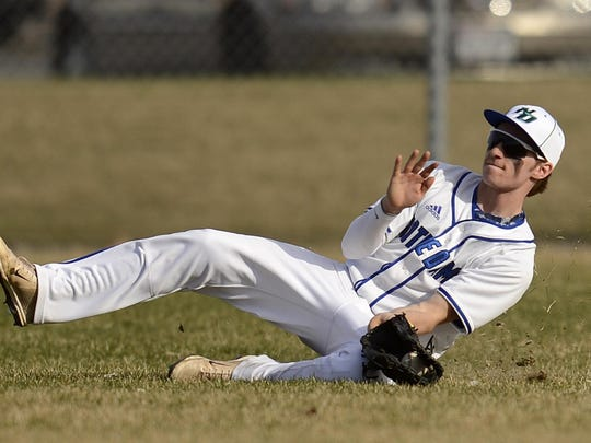 Green Bay Notre Dame senior outfielder Davis Elm makes a sliding catch during a Fox River Classic Conference game against Manitowoc earlier this season. Elm was the only player from the Tritons to earn all-conference recognition.
