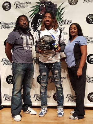 Palmetto Ridge receiver Kamonte Grimes (center) stands with his parents Torrey (left) and Prisca (right) after being named to the Freshman All-American Bowl on Oct. 25, 2017.