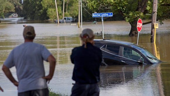 Residents survey the flood water on Old Jefferson Highway