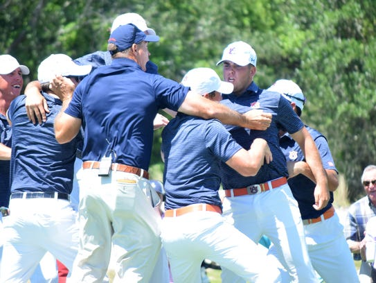 Auburn players and coaches celebrate on the 18th green