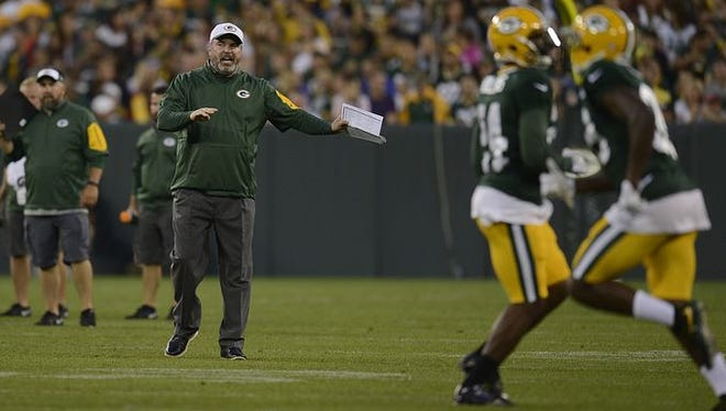 Green Bay Packers coach Mike McCarthy shouts instructions to his team during Saturday's Family Night practice at Lambeau Field.