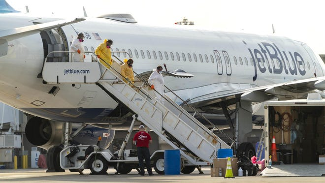 ACT Environmental Services crews clean a JetBlue plane after a flight from New York landed Wednesday night carrying a passenger who?d been infected with coronavirus at Palm Beach International Airport in West Palm Beach, Florida on March, 12, 2020.