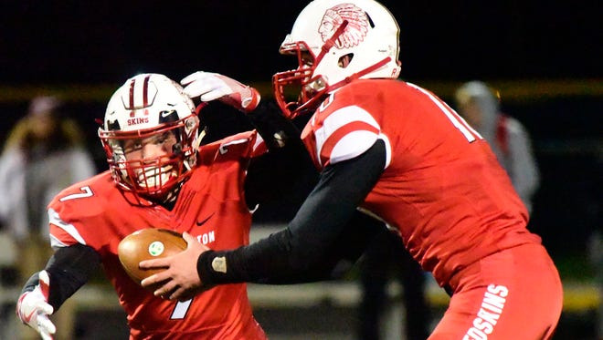 Port Clinton's Joey Brenner hands the ball to Emerson Lowe.