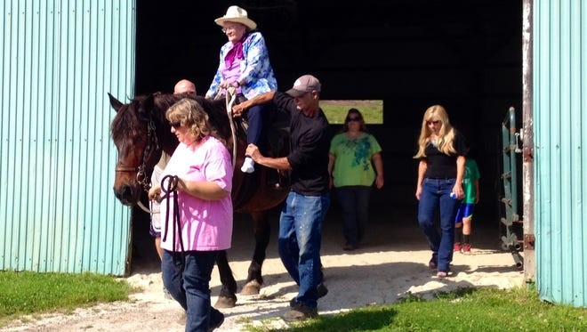 Accompanied by family and staff, Kay Liles rides Old Luke out of the barn at the Rainbow Riders stables in Troy. Kay celebrated her 90th birthday Wednesday with a horseback ride.