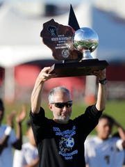 Winnebago Lutheran boys soccer coach David Haag holds up the state runner-up trophy in 2016.