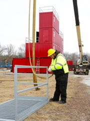 A construction worker from American Fire Training Systems hooks up the last piece of a fire training tower installed on the north side of Waupun to be used by the Waupun Fire Department for live fire training.