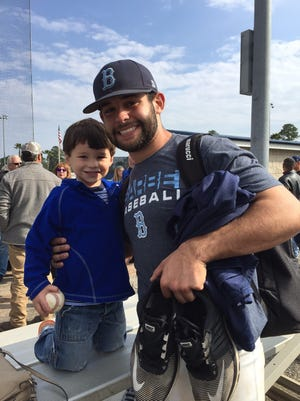 Parker Marcase, 4, who was diagnosed with diabetes Thursday afternoon, smiles and holds the game ball given to him Saturday by his cousin, Adam Goree, following Barbe's scrimmage victory over Concordia Lutheran.