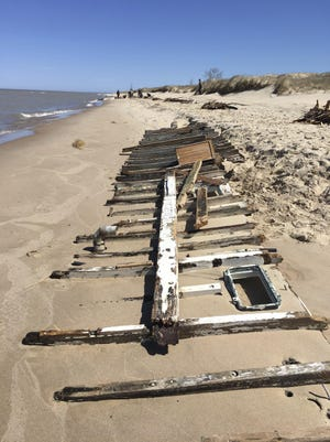 In a Saturday, April 22, 2017 photo, a portion of the hull of The Tica, a Traverse City-based vessel, is visible along the shoreline as debris from the ship, which broke up after it was grounded April 15 when it began taking on water. Authorities have closed the beach of Ludington State Park after the grounded, stranded pleasure boat broke apart just offshore. (Patti Klevorn/Ludington Daily News via AP)