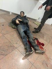 Sebastien Bellin lies wounded on the floor of the Brussels Airport in Brussels, Belgium, after explosions ripped through the departure hall on March 22, 2016.