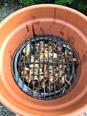 For a DIY smoker, place an electric burner on the bottom. A metal pie pan with soaked wood chips goes on top of the burner, then a grill grate. Top with another pot.