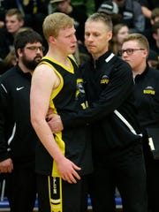 Waupun boys basketball player Owen Thuene gets consoled by coach Dan Domask on March 10, 2018, after losing to Kettle Moraine Lutheran in the WIAA Division 3 sectional finals in Whitefish Bay.
