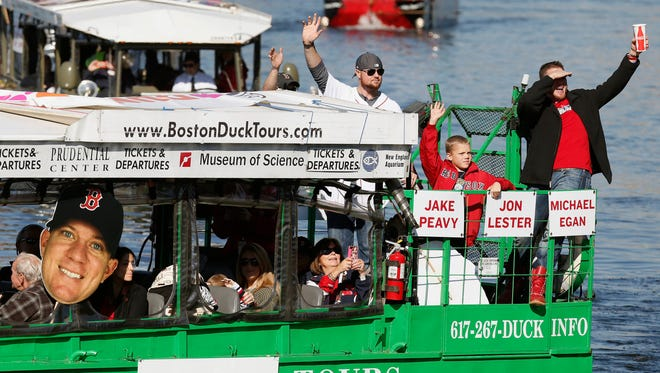 Jon Lester, top center, and Jake Peavy, right, wave from a duck boat on the Charles River during a rolling victory parade.