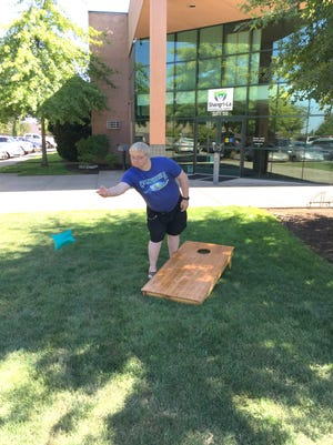 Tom, a person with disabilities, served by Shangri-La practices his cornhole toss on the lawn in front of the Shangri-La office in south Salem.