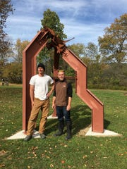 "Ben Cottom and Scott Oldfield stand near ""The Iroquois Walk,"" a sculpture by their former professor Allen Mooney, at the Summerhill Sculpture Center."