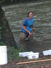 Turner Elementary teache Dolores Taitano goes knee-deep into the studies at Mill Creek during the school's Fall Seasonal Science Day.
