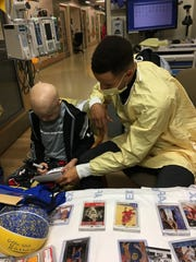 Brody Stephens and Steph Curry look over Brody's trading cards at Riley Hospital for Children.