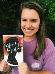 "Marion Reeves, 20, holds a copy of her book, ""Perfectly Imperfect."" The book chronicles her experiences with an eating disorder and depression, and was published in late April."