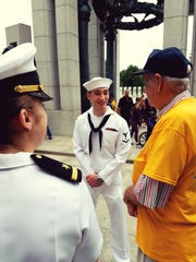Enlisted Navy personnel talk with a veteran at the National World War II Memorial.