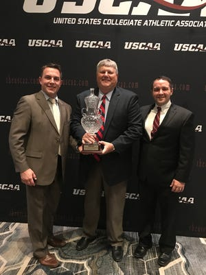 Cleary University athletic director Ward Mullens (center) received the USCAA Director's Cup from Michael Goodman (left), assistant executive director of the USCAA, and Mathew Simms (right), chief executive officer of the USCAA.