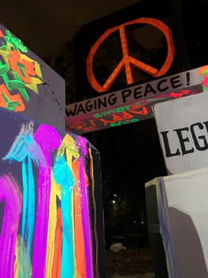 """Preparing for the March 3 workshop called """"Postcards and Posters for Peace,"""" local artist Perdita Ross uses an original collage technique with blacklight and florescent box paintings from performances on First Fridays."""