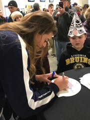 Allison Schmitt signs a swim cap for 9-year-old Colin Witt of Livonia during a recent appearance at USA Hockey Arena in Plymouth.