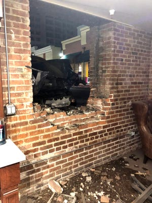Vinnie Gravallese, owner of Derby Supply Co. barbershop, surveys the damage down to his store when a car crashed into the wall the morning of March 7, 2018. The car destroyed a window and flying brick destroyed custom furniture and antiques used to decorate the store.