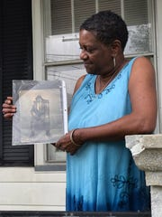 Alrita Pollard Lewis holds up a photo of her grandfather Lent Shaw in front of her home in Evansville, Indiana.