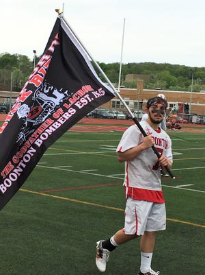 Boonton senior Jad Elsahely led the lacrosse team onto the field carrying the Dick Rizk memorial flag.