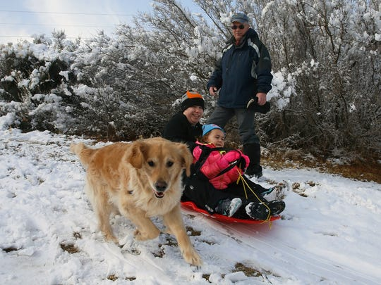 Megan Riggs prepares to sled down a hill with her daughter, Chloe Schlotthauer, and dog, Maddie, while Eric Schlotthauer looks on at Kiwanis Park in Farmington on Tuesday.