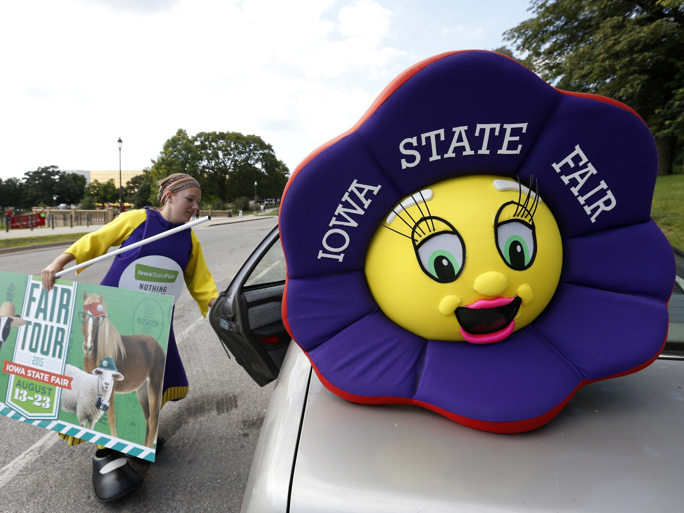 Allison Edwards pulls the Iowa State Fair banner out of her car as she puts on the purple ribbon mascot costume on Wednesday, Aug. 12, 2015 before the State Fair parade along Grand Avenue in Des Moines.