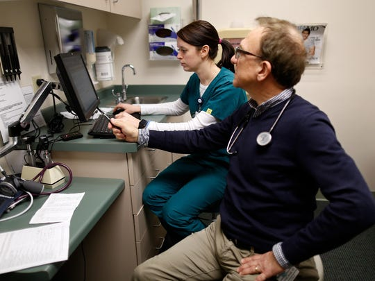 Family Physician Dr. James Jerzak works with Medical Assistant Jamie Burroughs on keeping records during a visit with a patient, the two are part of an integrated care team at Bellin family practice clinic in Ashwaubenon, Wis. on Monday, Jan. 11, 2016.