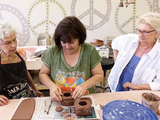 Emily Vizina, center, leads a ceramics class at Emily
